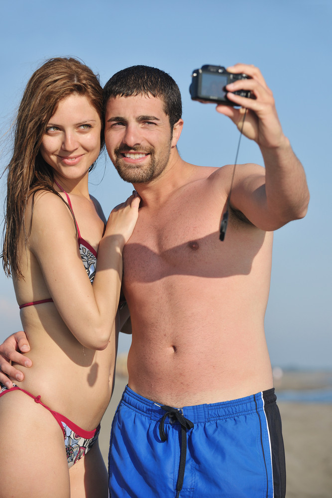 Happy Young Couple In Love Taking Photos On Beach