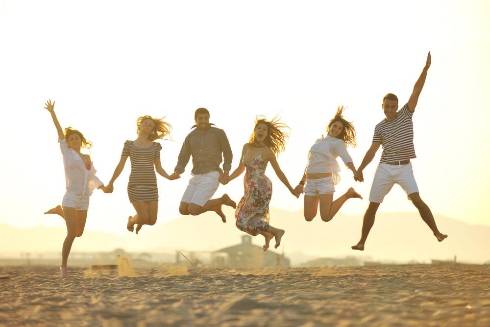 Glückliche Gruppe der jungen Leute haben Spaß auf Strand