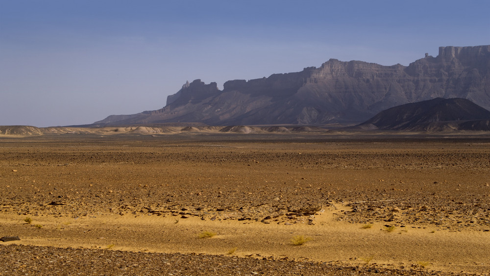 Sandy, barren desert and distant rocky cliffs