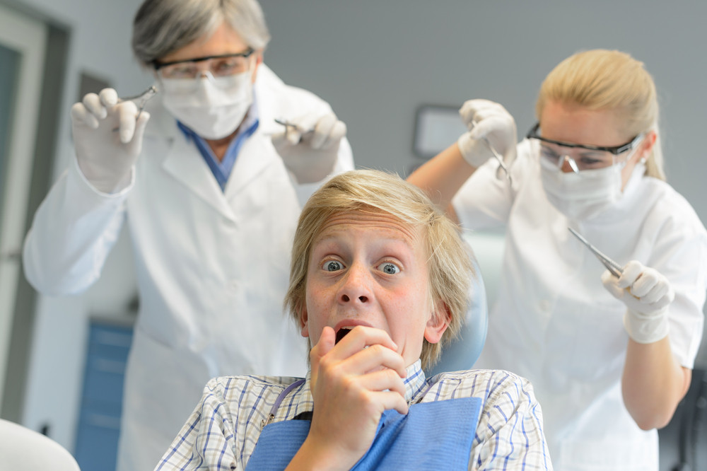 Scared Teenage Patient Boy At Dental Clinic Frightening Dentist Assistant