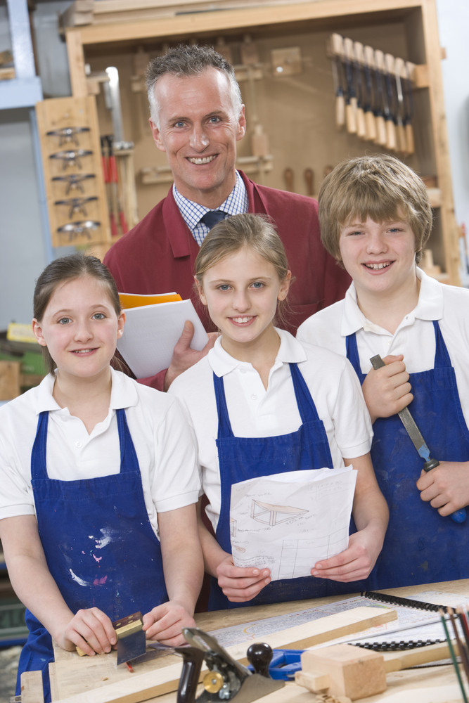 Schoolchildren and teacher in woodwork class