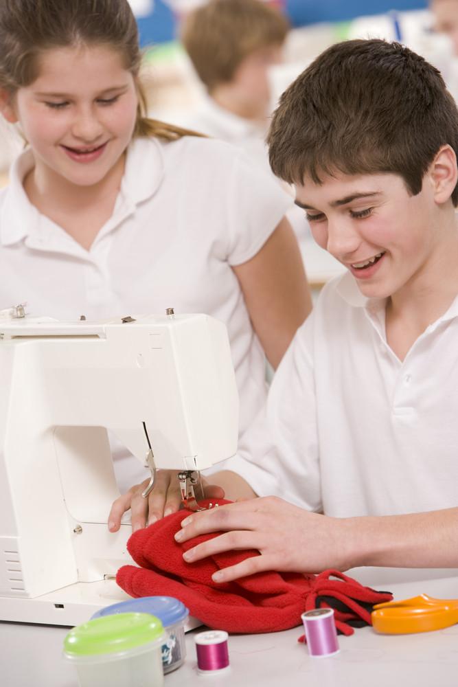 Schoolchildren using a sewing machine in sewing class