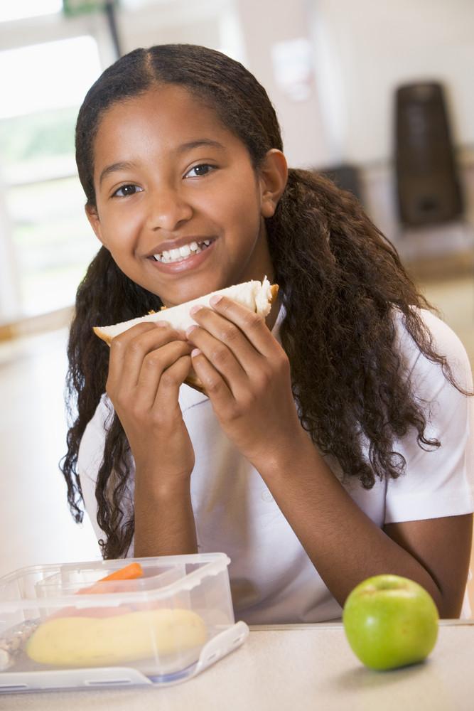 Schoolgirl enjoying her lunch in a school cafeteria