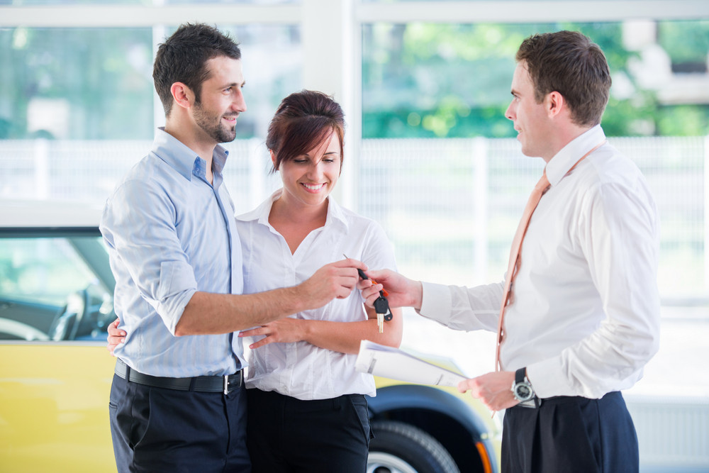 Seller handing car keys to a happy couple in a salon