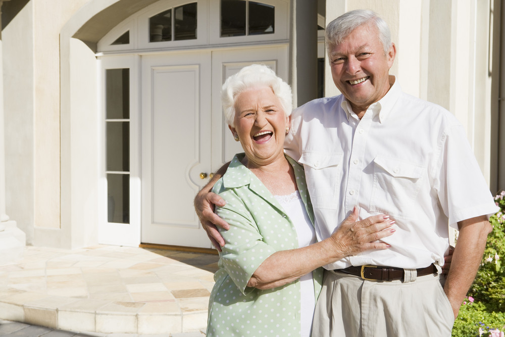 Senior couple embracing outside house