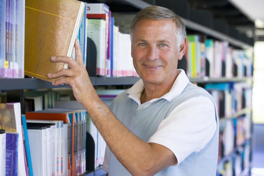 Senior man pulling a library book off shelf