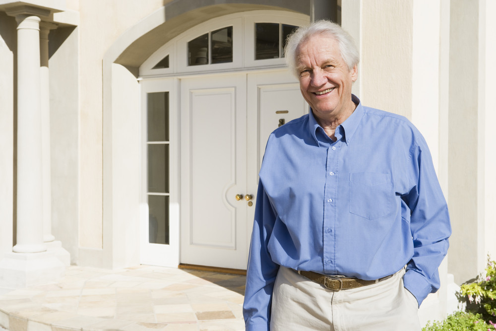 Senior man standing outside front door of house
