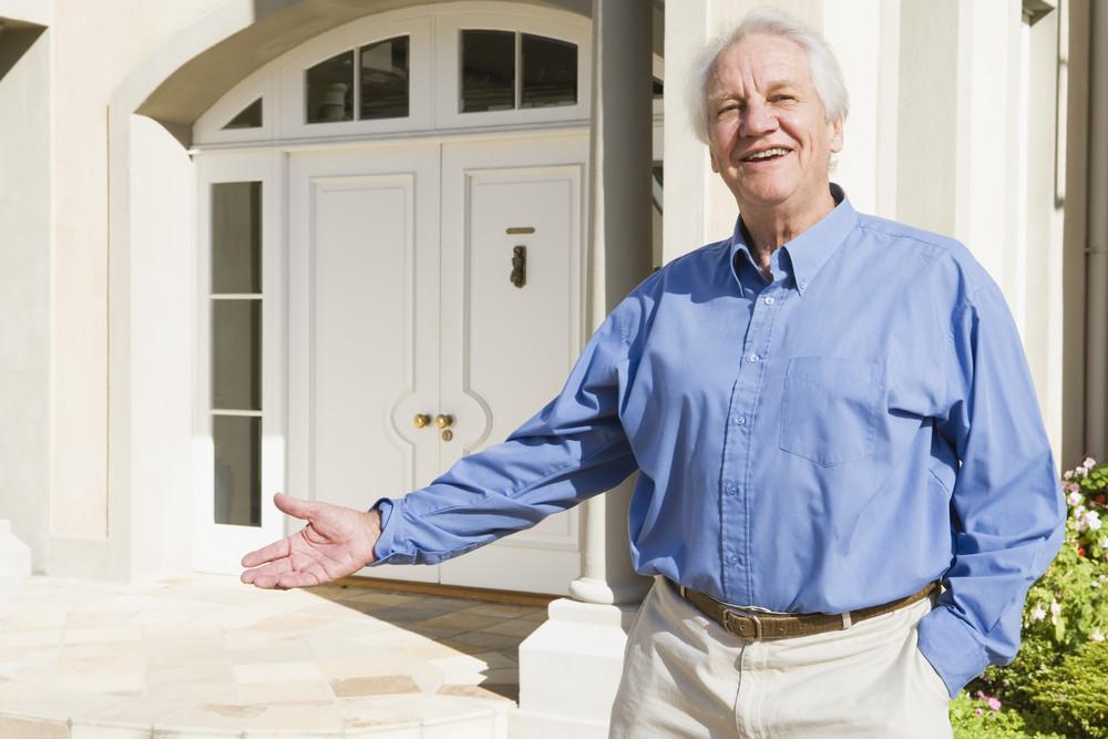 Senior man welcoming visitor to home