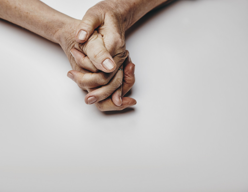 Senior woman's hands isolated on grey background. Hands of a relaxed old female with copy space. Praying hands.