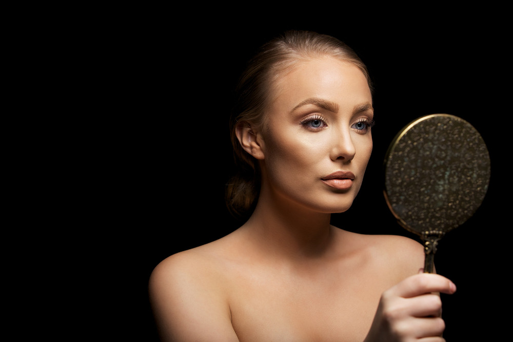 Sensual young female model looking in hand mirror. Beautiful young girl checking her make up against black background with copyspace.