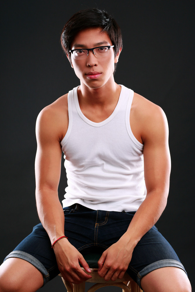 Serious asian man in glasses sitting on the chair over black background