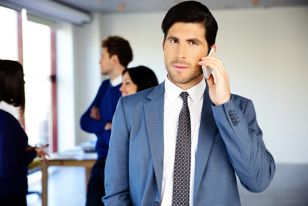 Serious businessman talking on the phone in front of colleagues