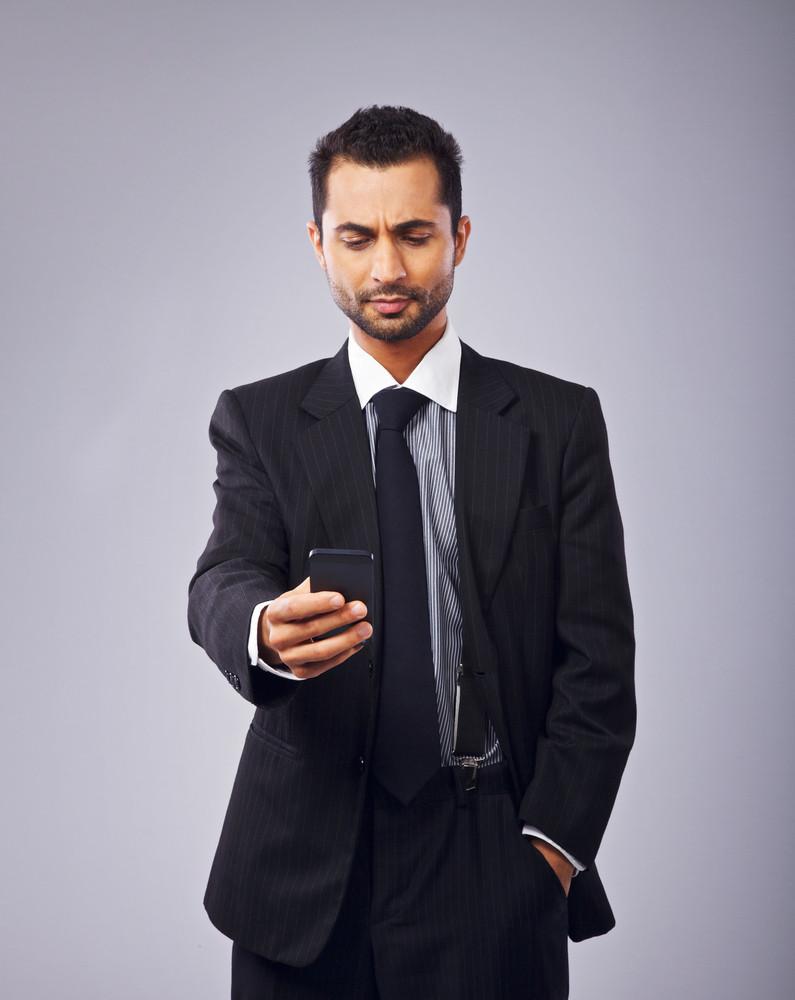 Serious executive reading a text message