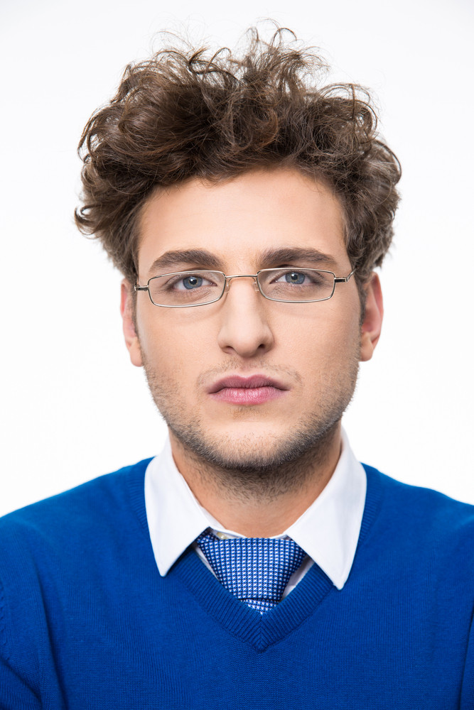 Serious young businessman in glasses loooking at the camera
