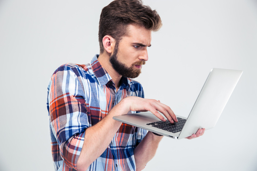 Serious young man standing and using laptop