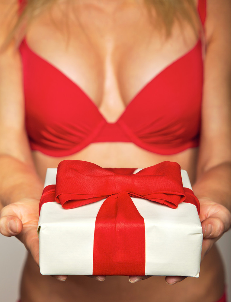 Sexy female in red underwear offering a white gift wrapped in red ribbon