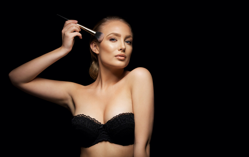 Sexy young woman wearing black bra applying foundation with a make up brush against black background with copyspace. Sensual lingerie model applying make up.
