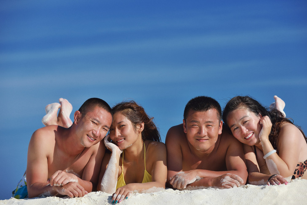 Group of happy young people have fun on beach