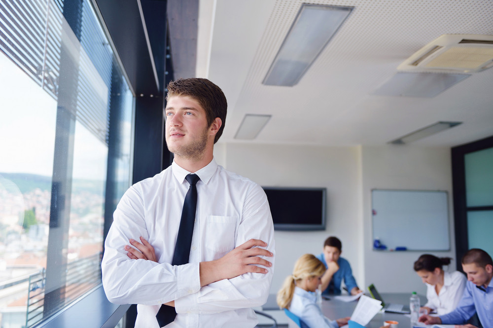 Business man in a meeting in offce with colleagues in background