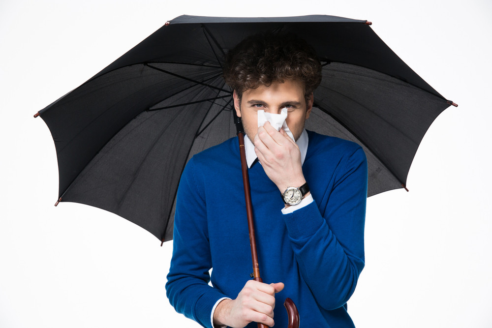Sick business man holding umbrella and blowing nose