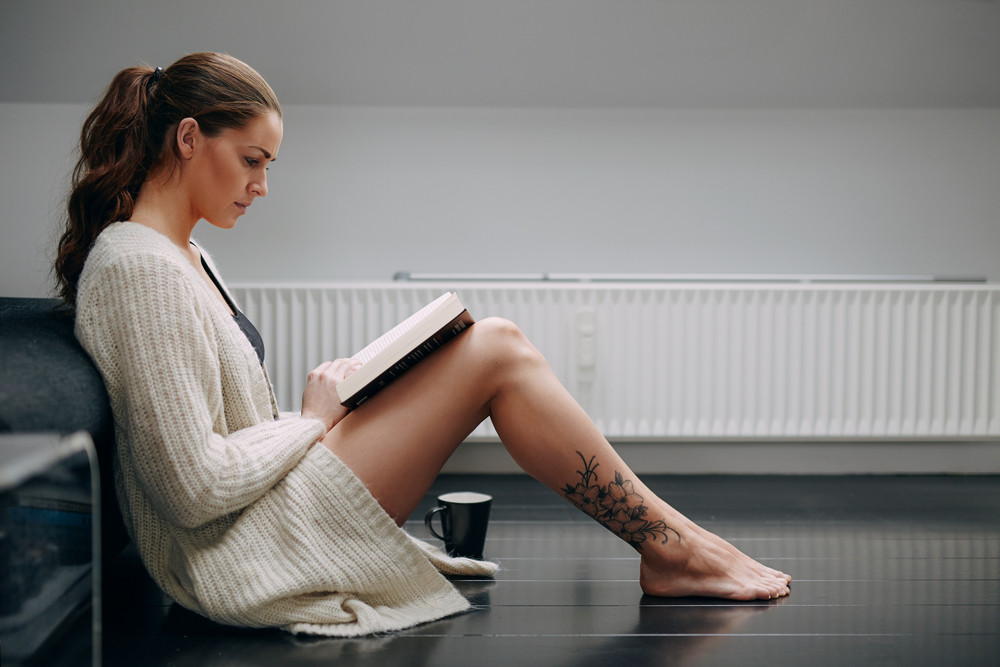 Side view of beautiful young lady reading a book. Caucasian female model at home sitting on floor by a couch with a novel.