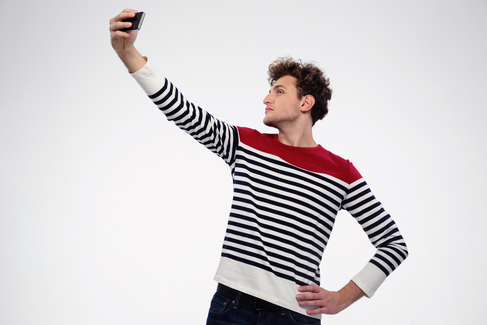 Side view portrait of a man making selfie photo over gray background