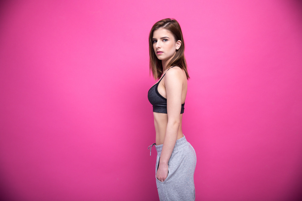 Side view portrait of a sports woman over pink background