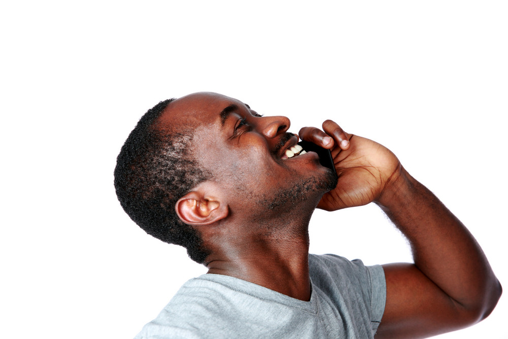 Side view portrait of african man talking on the phone isolated on a white background