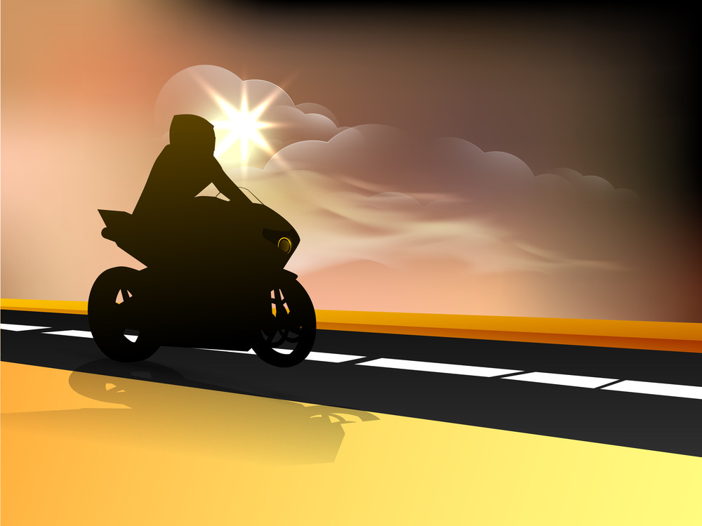 Silhouette Of A Motorbiker Riding On Track At Evening Background.