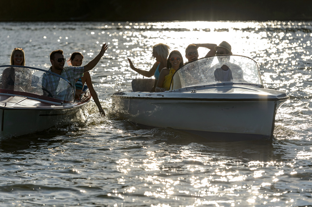 Silhouette of young people enjoying summer motorboat on lake