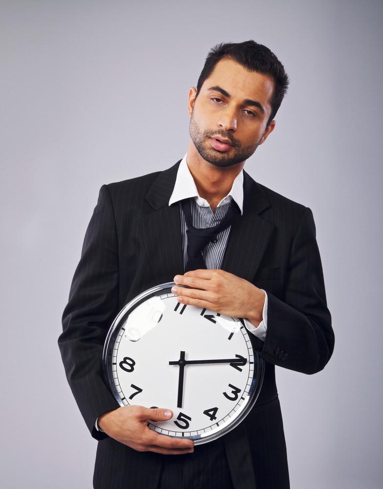 Sleepy office worker holding a clock