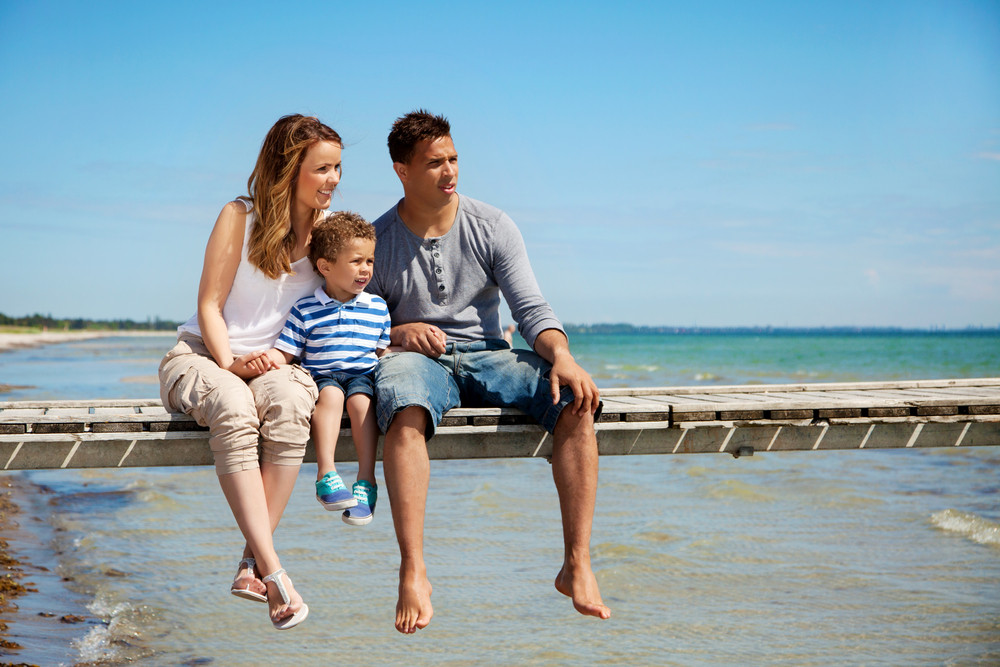 Small family of three enjoying their summer vacation by the beach
