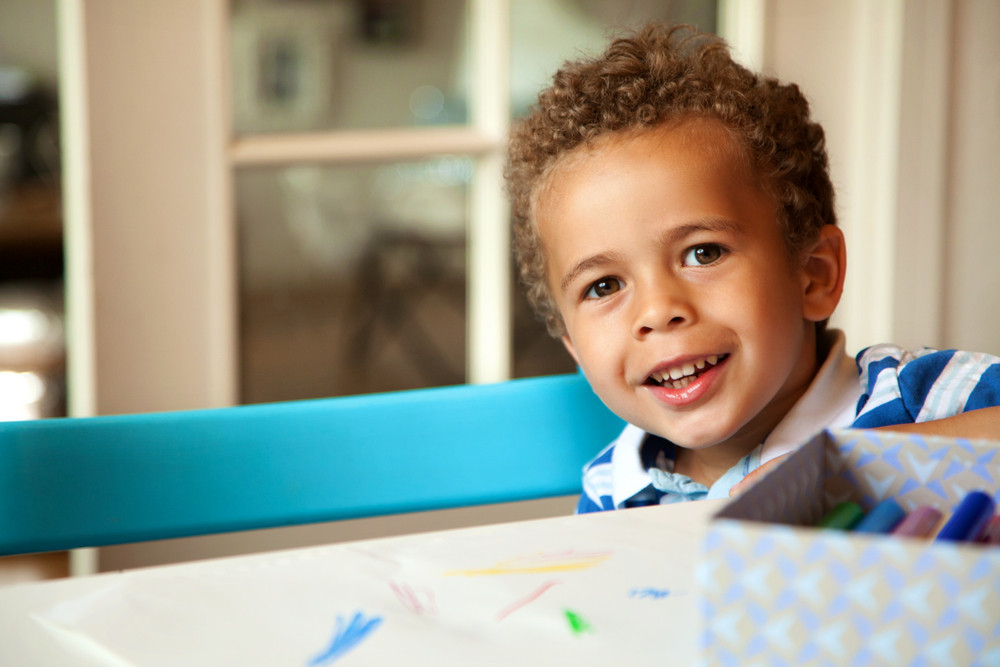 Smiling African American boy sitting on a chair and getting ready for his lesson