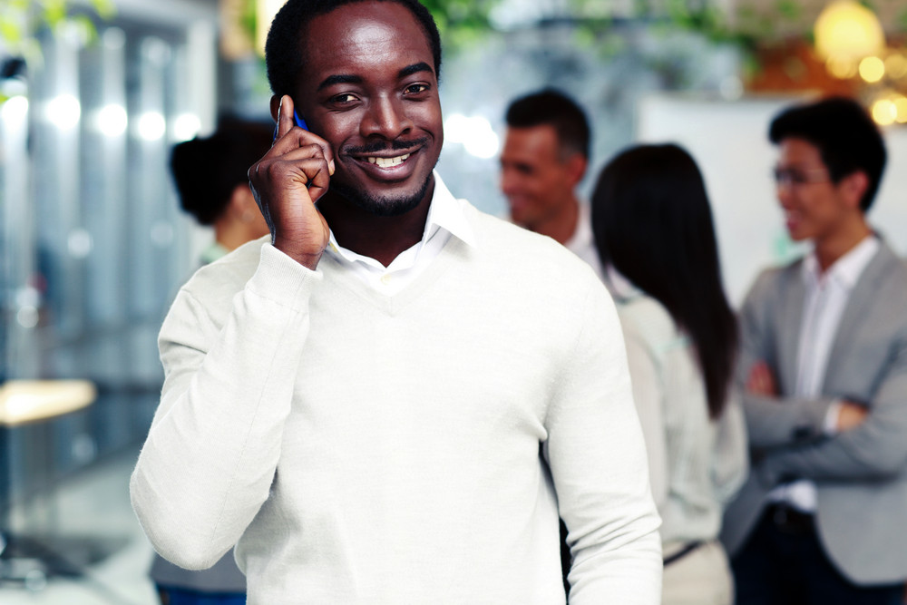 Smiling african businessman talking on the smartphone in front of colleagues