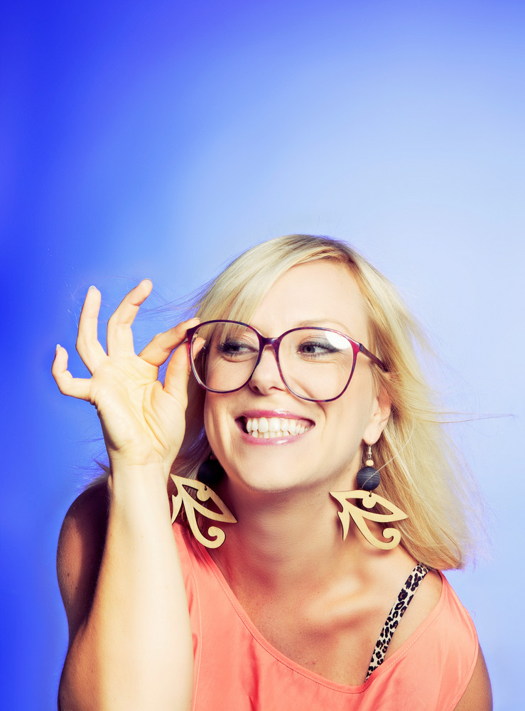 Smiling and playful woman wearing a large nerd glasses