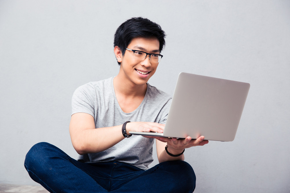 Smiling asian man using laptop