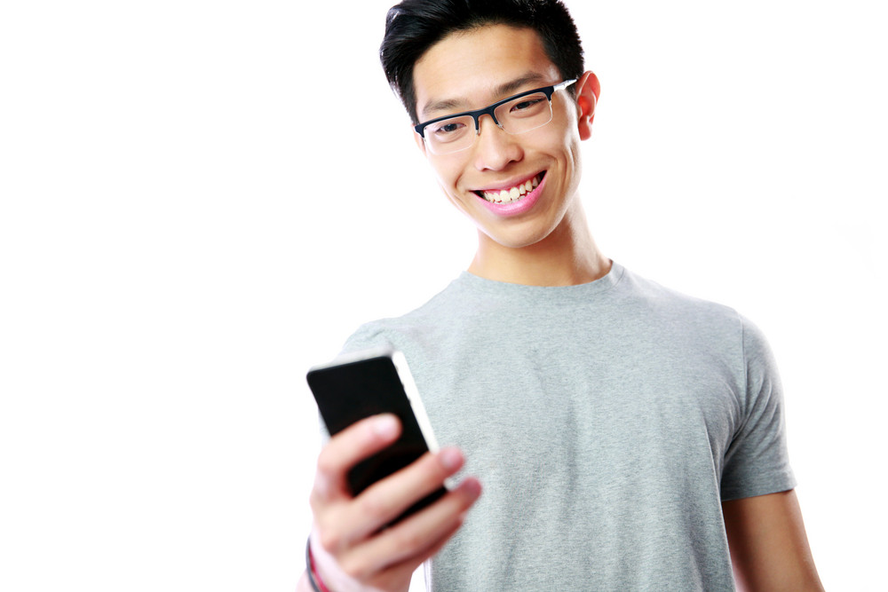 Smiling asian man using smartphone on gray background