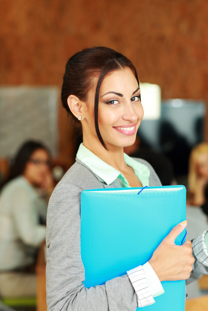Smiling beautiful businesswoman standing with folder in office