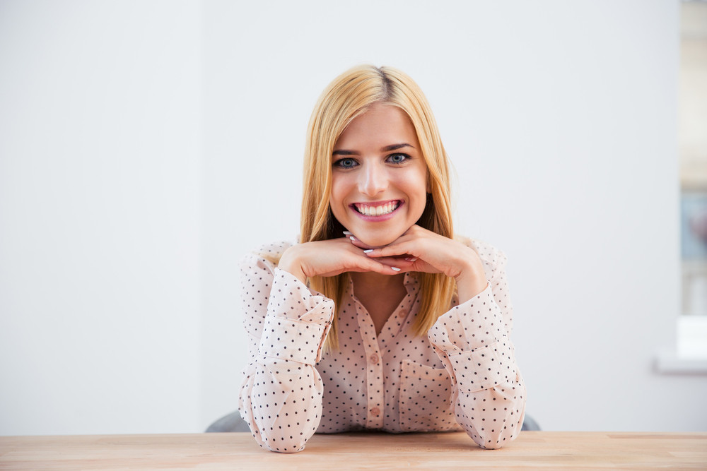 Smiling blonde businesswoman sitting at the desk