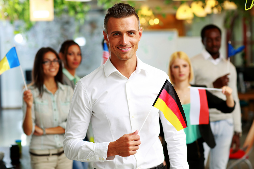 Smiling businessman holding flag of Germany in front of colleagues