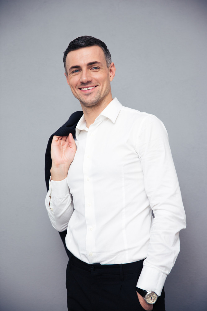 Smiling businessman holding jacket on shoulder