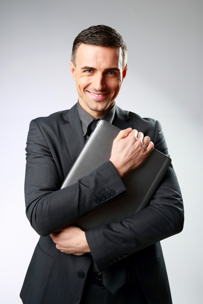 Smiling businessman holding laptop on gray background