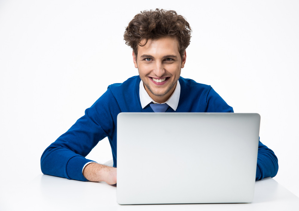 Smiling businessman sitting at the table with laptop and looking at the camera