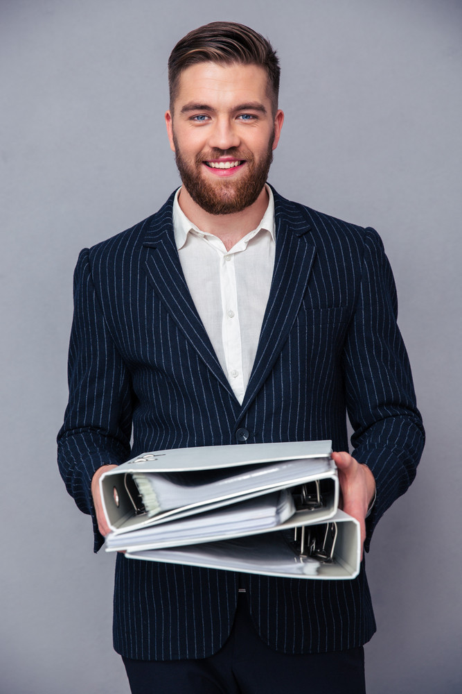 Smiling businessman standing with folders