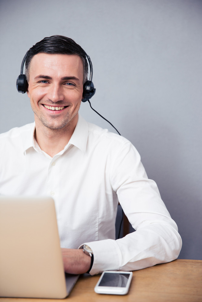 Smiling businessman with laptop and headphone