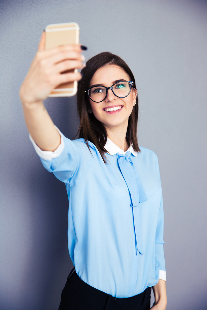 Smiling businesswoman making selfie photo