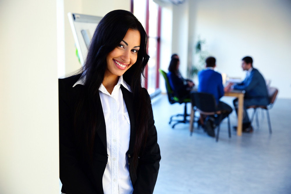 Smiling businesswoman standing in front of a business meeting