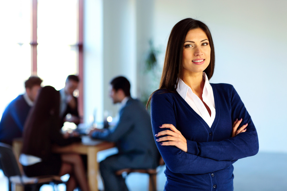 Smiling businesswoman standing with arms folded in front of colleagues