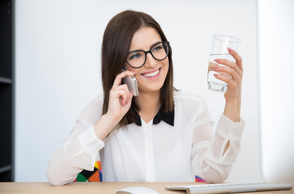 Smiling businesswoman talking on the phone and holding glass