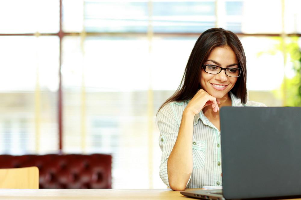 Smiling businesswoman working on the laptop at office